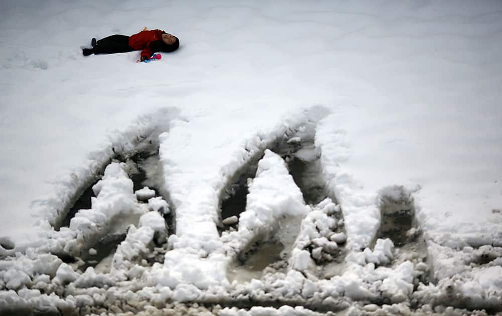 A child plays at a parking lot covered with snow in Yokohama, Japan, as the Pacific coast of eastern and western Japan was hit by snow.