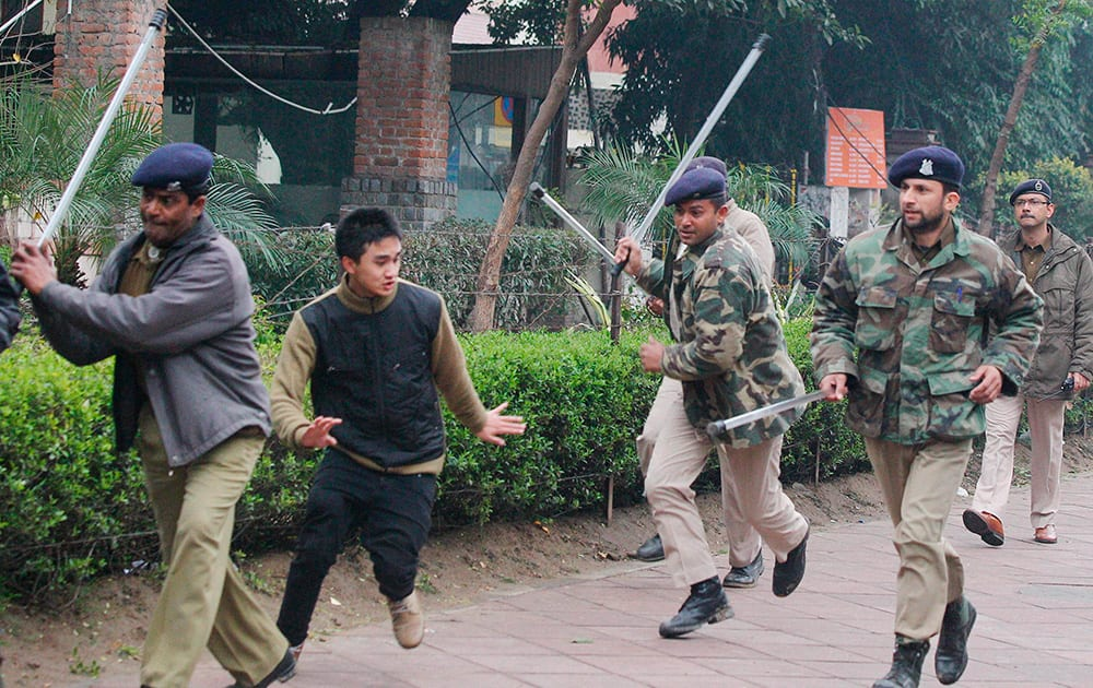 Securitymen charge Northeast students near Parliament during a protest over the killing of Nido Tania in New Delhi.
