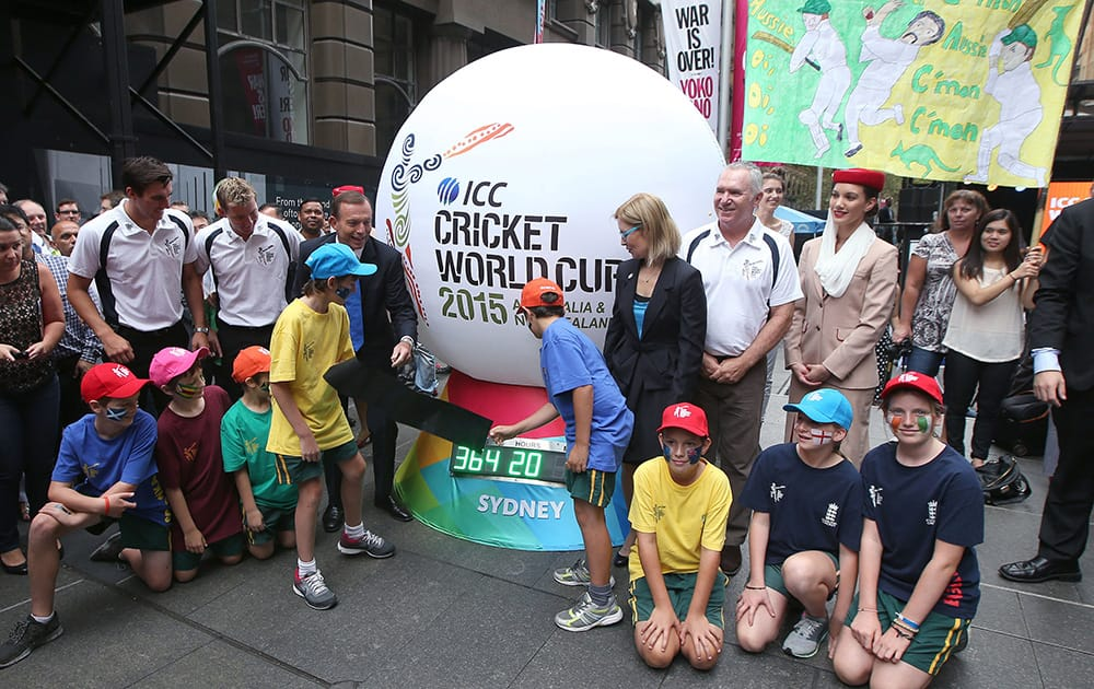 Australian Prime Minister Tony Abbott and two children unveil a countdown clock during a ceremony in Sydney, marking one year to the start of the 2015 ICC World Cup Cricket tournament.