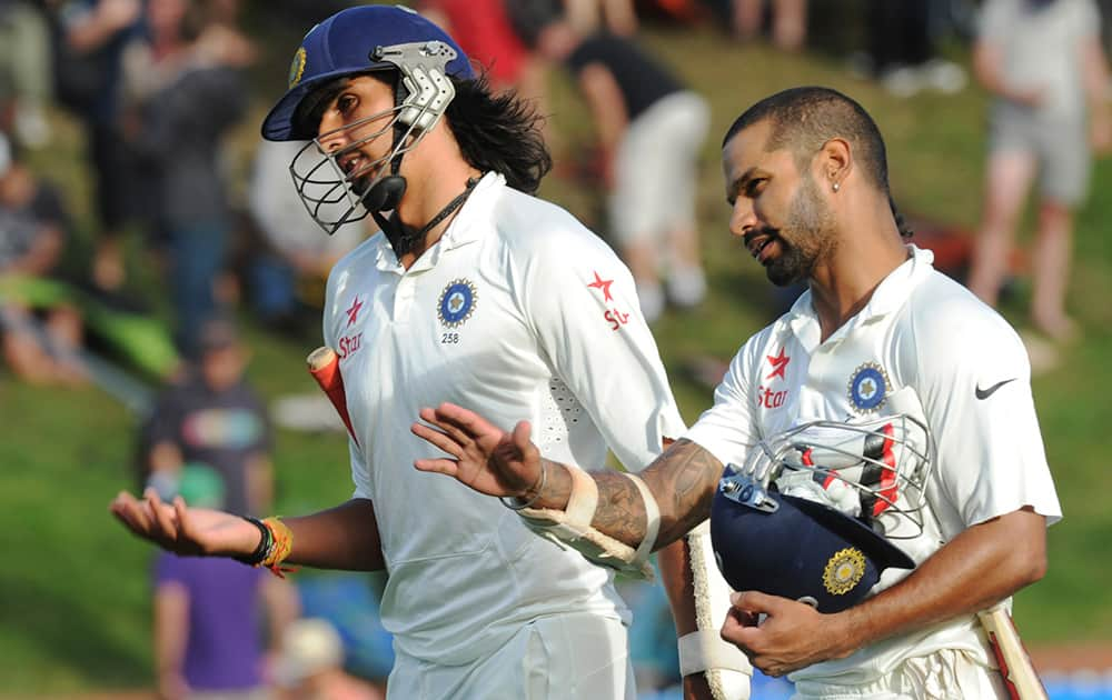 Ishant Sharma and Shikar Dhawan leave the pitch at the end of play against New Zealand on the first day of the second cricket test in Wellington, New Zealand.