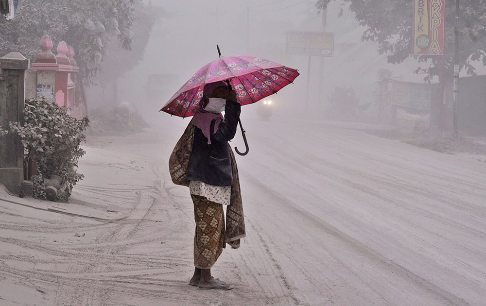 A women walks on a road covered with volcanic ash following an eruption of Mount Kelud, in Yogyakarta, Indonesia.