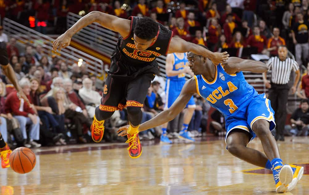 Southern California guard Brendyn Taylor, left, and UCLA guard Jordan Adams dive for a loose ball during the first half of an NCAA college basketball game.