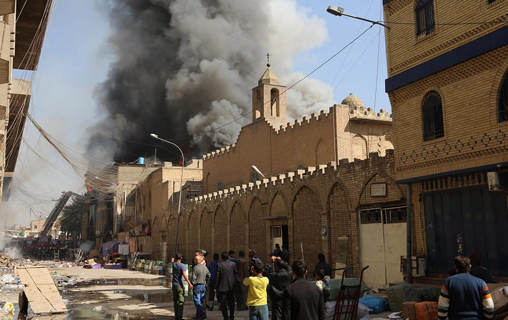 Civilians gather as firefighters try to extinguish fire after a two bombs went off in Baghdad, Iraq.
