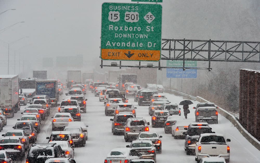 A motorist, right, who abandoned their vehicle, walks through stopped traffic on northbound Interstate 85 during a winter storm in Durham, N.C.