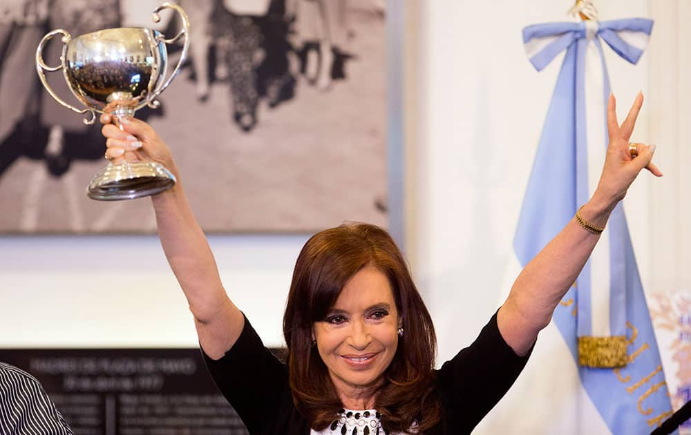 Argentine President Cristina Fernandez lifts a trophy given to her by a supporter during an event at the Casa Rosada government palace in Buenos Aires, Argentina.