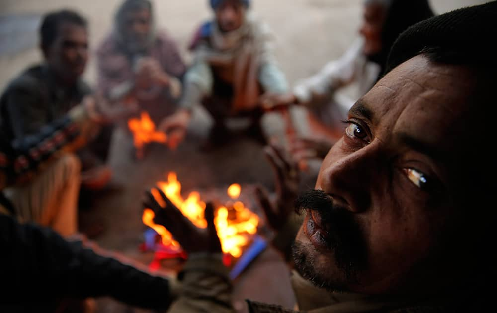 Men warm themselves around a fire on a cold morning in the old quarters of New Delhi. The capital witnessed a chilly morning Wednesday.