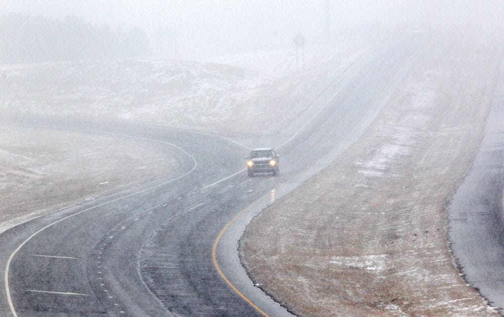 A vehicle drives through falling snow on the U.S. 421 bypass in Sanford, N.C.