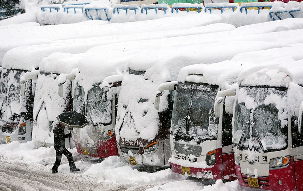 A man walks past snow-covered buses as more than one meter (3.3 feet) of snow fell last week in Gangneung, South Korea.