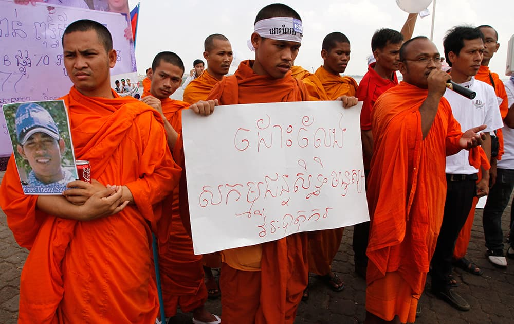 Buddhist monks hold the portrait of a detainee and a banner reading `Free human rights activists, hero workers` during a prayer in a rally calling for the release of the detained anti-government protesters, in front of the Royal Palace in Phnom Penh, Cambodia.