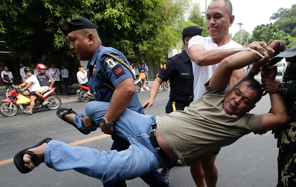 Presidential security arrest a farmer-protester after their group was able to sneak into the tight security to hold a `lightning rally` right at the gates of Malacanang Palace in Manila, Philippines to demand the President award them the farmlands allegedly promised them through the Comprehensive Agrarian Reform Program of the government.