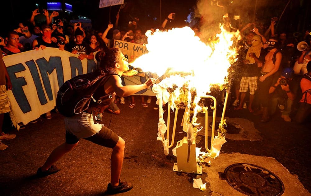A girl spits fire on a bus turnstile set on a street in protest against the increase on bus fares in Rio de Janeiro, Brazil.