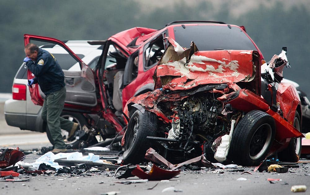 Officials investigate the scene of a multiple vehicle accident where six people were killed on the westbound Pomona Freeway in Diamond Bar, Calif.