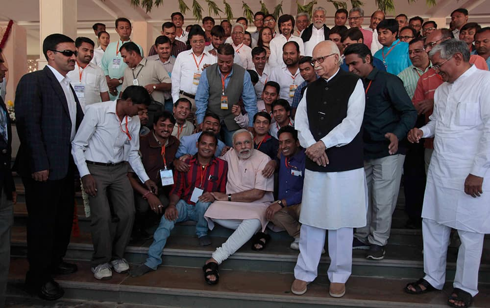 Narendra Modi and senior leader Lal Krishna Advani pose for photographs with party workers during the inauguration party`s new state headquarters building in Gandhinagar.
