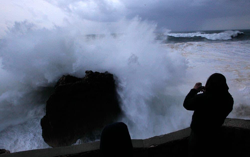 A man takes photographs of huge waves hitting rocks at the Nazare lighthouse, outside the fishing village of Nazare, on the central coast of Portugal.