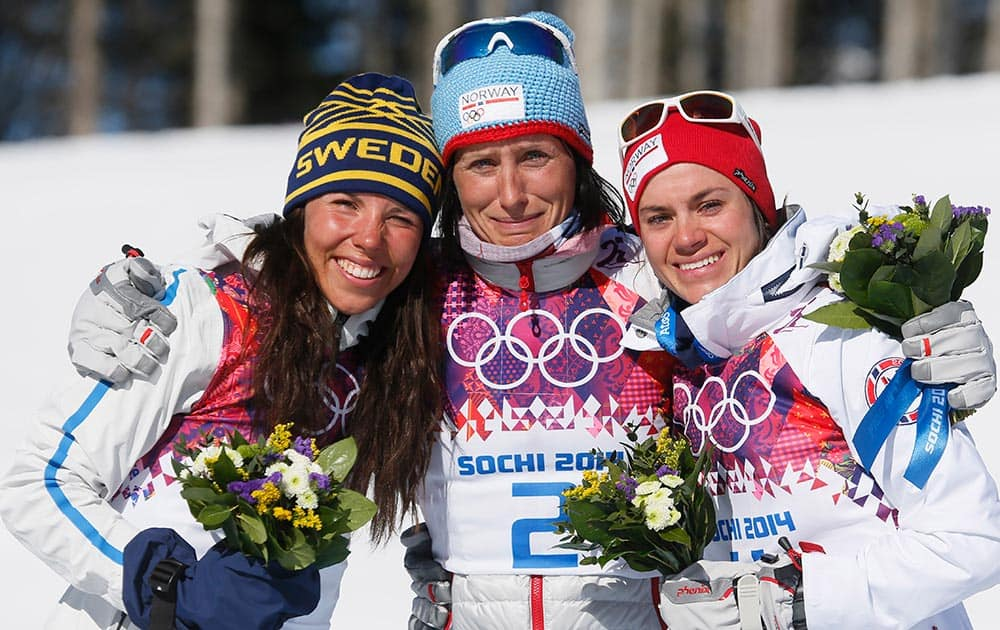 Norway`s gold medal winner Marit Bjoergen is flanked by Sweden`s silver medal winner Charlotte Kalla, left, and Norway`s bronze medal winner Heidi Weng after the flower ceremony for the women`s cross-country 15k skiathlon at the 2014 Winter Olympics, in Krasnaya Polyana, Russia.