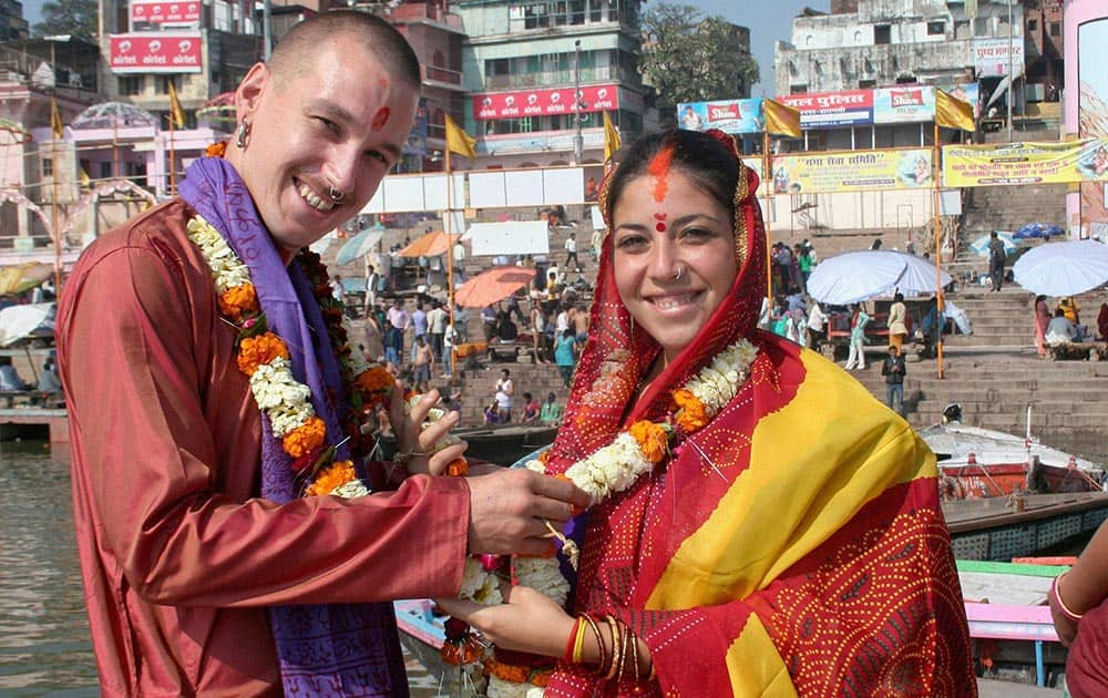 A foreign couple getting married according to Hindu traditions on the bank of Ganga River in Varanasi.