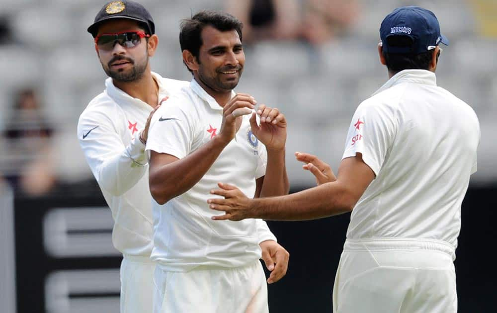 India's Mohammed Shami, center, celebrates the dismissal of New Zealand's Peter Fulton for 5 on the third day of the first cricket test, Eden Park in Auckland.