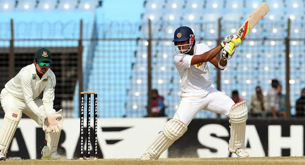 Sri Lanka's Dinesh Chandimal, right, plays a shot as Bangladesh's Shamsur Rahman watches on the fourth day of the second test cricket match between them in Chittagong, Bangladesh.