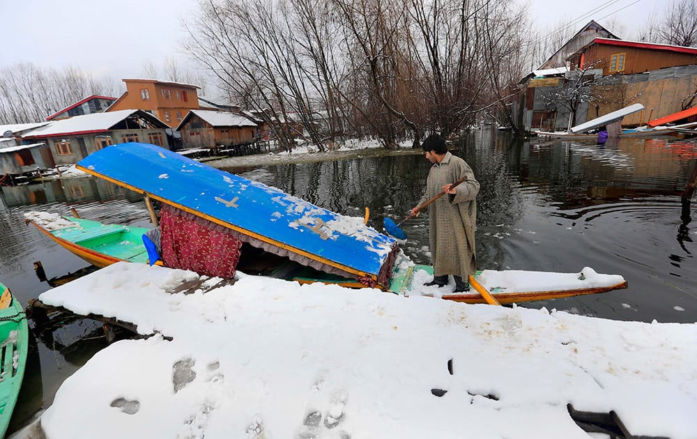 A Kashmiri boatman clears snow from the roof of his shikara, traditional gondola, on the shore of Dal Lake after fresh snowfall in Srinagar.