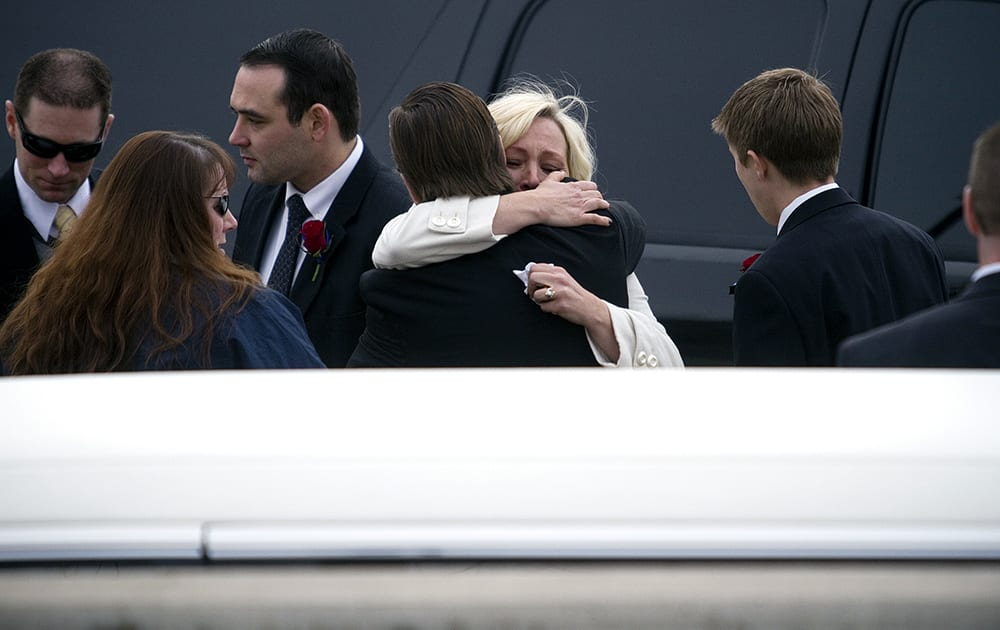 Utah County Sheriff`s Sgt. Cory Wride`s widow Nannette Wride receives a hug from her brother-in-law Ryan Wride after the funeral service for her husband was held at the UCCU Center in Orem, Utah.