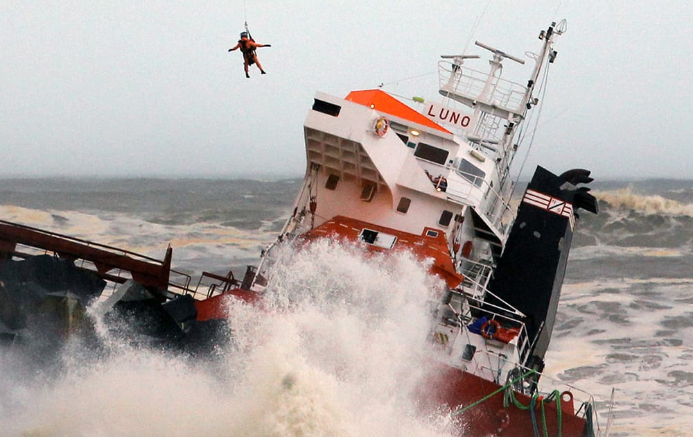 A helicopter lowers a rescue worker toward a Spanish cargo ship the Luno that slammed into a jetty in choppy Atlantic Ocean waters off Anglet, southwestern France.