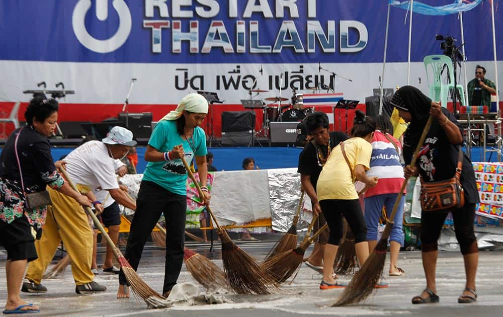 Volunteer street cleaners brush the main anti-government protest site with detergent and brooms in Bangkok, Thailand.