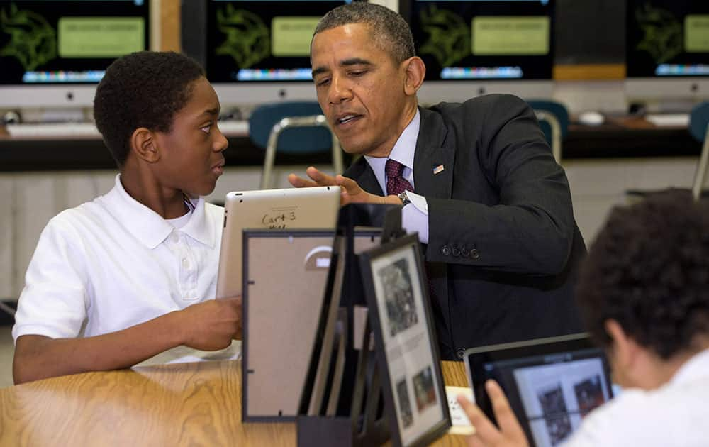 President Barack Obama looks at a student`s iPad project at Buck Lodge Middle School in Adelphi, Md., where he spoke about his ConnetED goal of connecting 99% of students to next generation broadband and wireless technology within five years.
