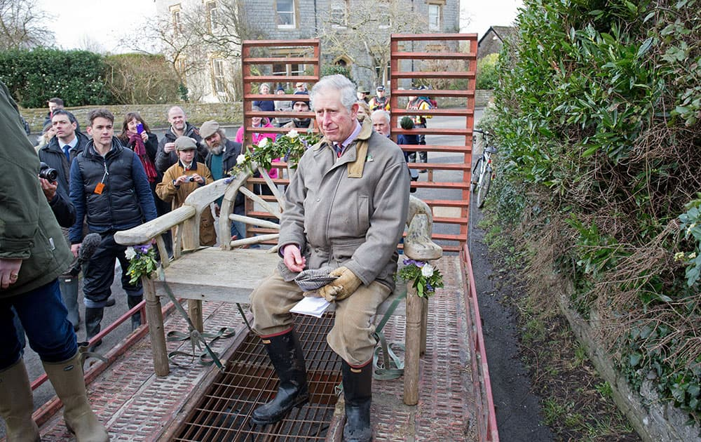 Britain`s Prince Charles sits on a garden bench on a tractor-towed trailer as he travels through the flood-hit community of Muchleney, southwest England.