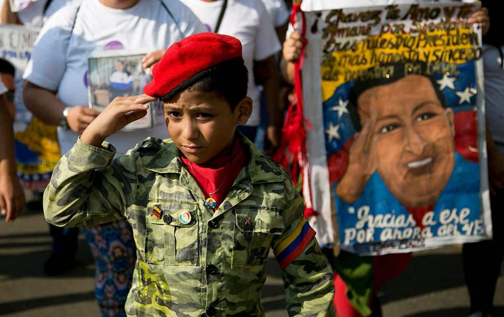 A boy dressed in a military-like uniform and a red beret salutes during an event commemorating the anniversary of a failed coup attempt led by the late President Hugo Chavez, in Caracas, Venezuela.