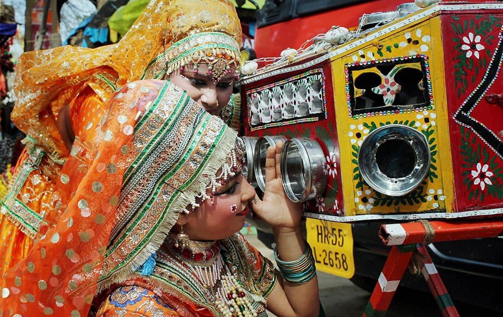 Brij artists see through a bioscope at the 28th Surajkund International Crafts Mela in Faridabad.