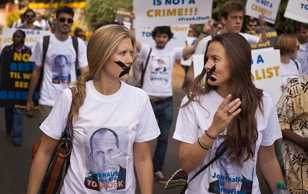 Members of the media march with black tape across their mouths, signifying the silencing of the media, and wearing tee-shirts showing detained Al-Jazeera journalist Peter Greste, at a demonstration by Kenyan and Nairobi-based foreign media calling for the release of Greste and his colleagues, outside the Egyptian embassy in Nairobi, Kenya.