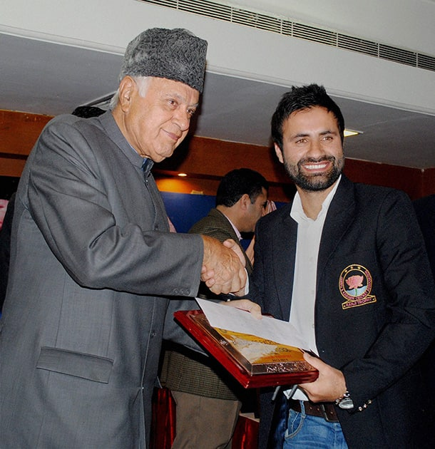 Union Minister for New and Renewable Energy and President of Jammu & Kashmir Cricket Association (JKCA) Farooq Abdullah (L) felicitates Jammu and Kashmir captain Parvez Rasool during a welcome party for Ranji trophy team in Jammu.