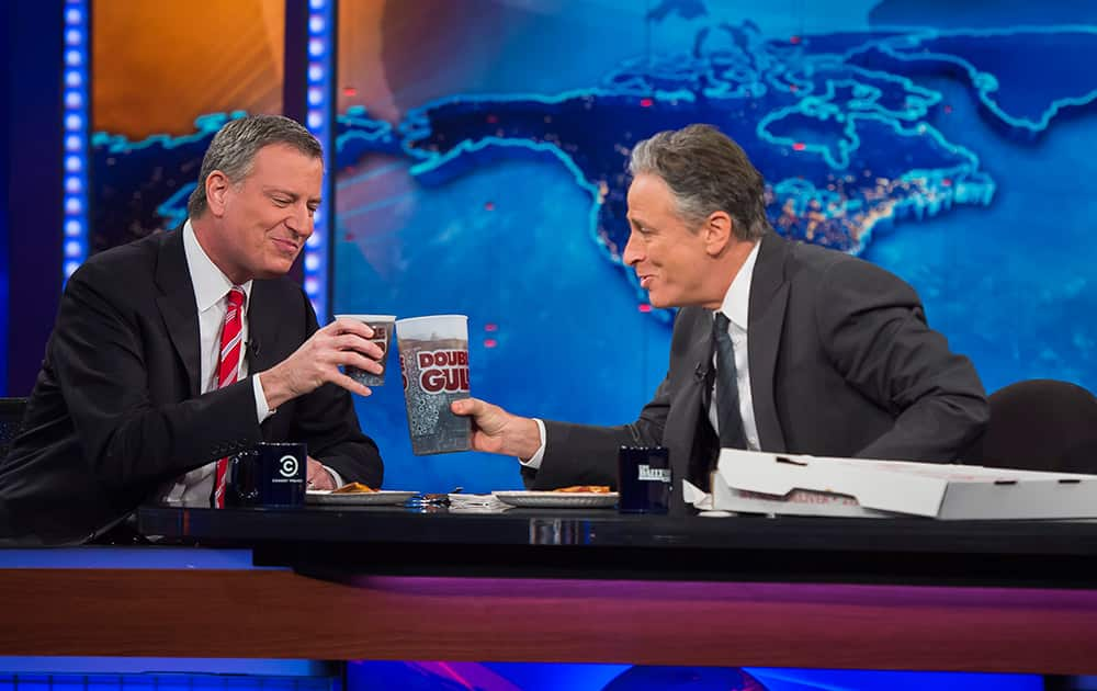 New York Mayor Bill de Blasio, left, shares pizza and soda with host Jon Stewart on Comedy Central`s `The Daily Show` 2014 in New York.