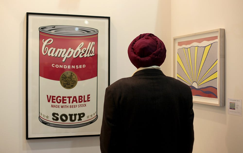 A visitor views art by Roy Lichtenstein, on right and Andy Warhol, left, displayed at the India Art Fair in New Delhi.