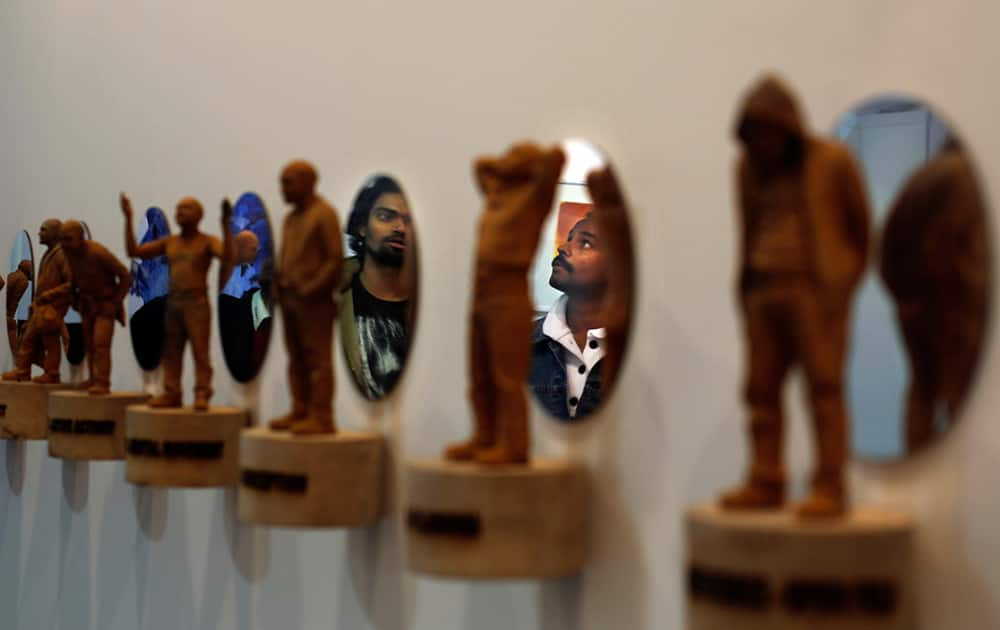 Visitors are reflected on mirrors as they look at an artwork at the sixth India Art Fair in New Delhi.