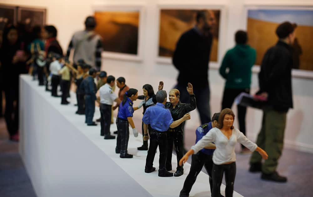 Figurines depicting frisking are at display at the sixth India Art Fair in New Delhi.