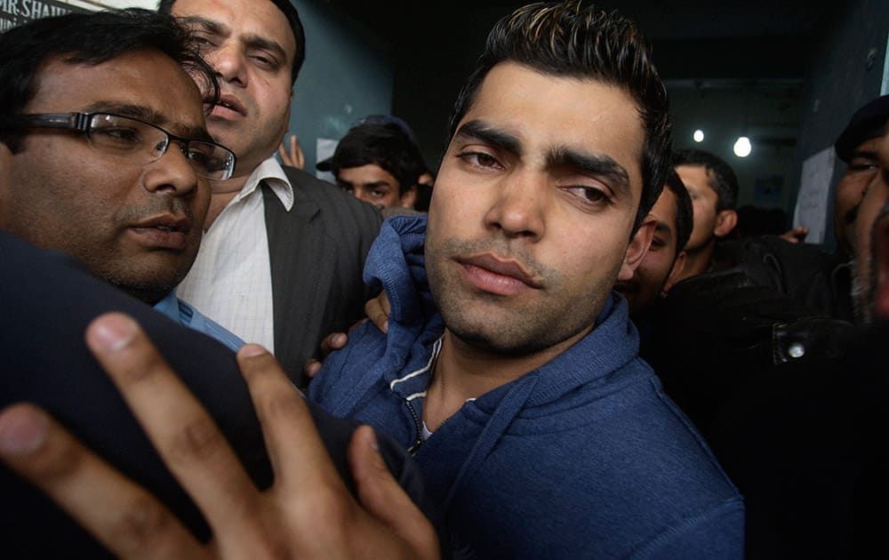 Pakistani cricketer Umar Akmal trys to avoid the media as he leaves as he leaves a court after being granted bail in Lahore. Pakistan cricketer Umar Akmal was released late Saturday after a police official filed for the middle-order batsman`s bail-out for his run-in with a traffic sergeant.