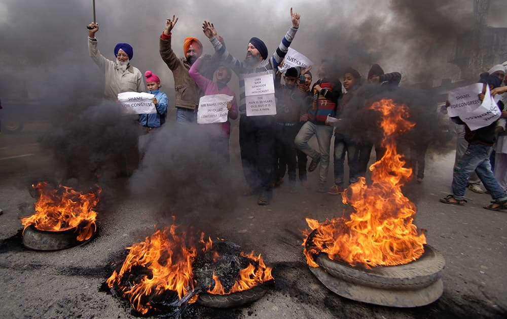 Sikh protestors shout slogans and burn tires during a protest against Congress party leader Rahul Gandhi for his recent remark on the country`s 1984 anti-Sikh riots, in Jammu, India.