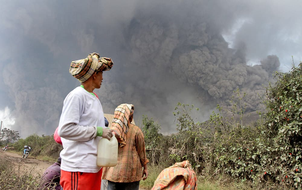 Villagers watch as Mount Sinabung releases pyroclastic flows during an eruption in Namantaran, North Sumatra, Indonesia.