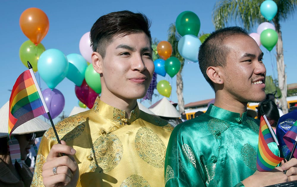 Timothy Truong, left, and Peterson Pham march with others in the Lunar New Year parade, as part of the gay and lesbian group Viet Rainbow of Orange County, in Westminster, Calif.