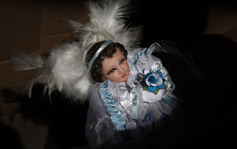 A figure of baby Jesus dressed as an angel is held by its owner at a stand that sells clothes for baby Jesus dolls in Mexico City.