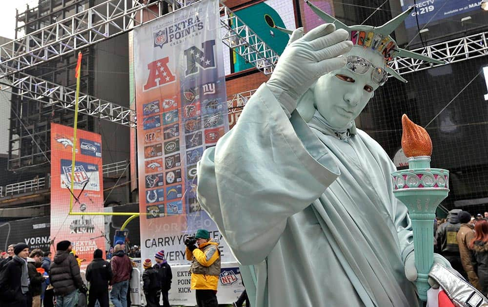 A man dressed as the Statue of Liberty poses for photos with football fans along Super Bowl Boulevard, in New York.