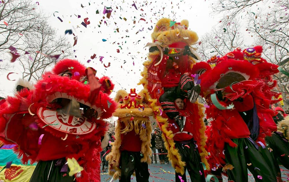 Lion dancers perform during the Asian Lunar New Year Firecracker Ceremony and Cultural Festival, in Roosevelt Park, in New York`s Chinatown.