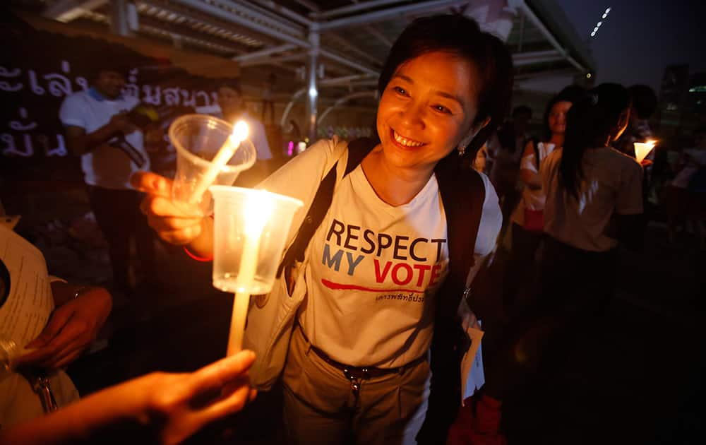 Members of Thailand`s `White Shirt` movement light candles during a vigil to demand democratic elections and political reforms in Bangkok, Thailand.