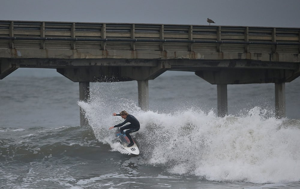 A surfer rides unusually high surf under the Ocean Beach Pier, in San Diego. For the first time in months the weather forecast in Southern California predicts rain and a winter storm.