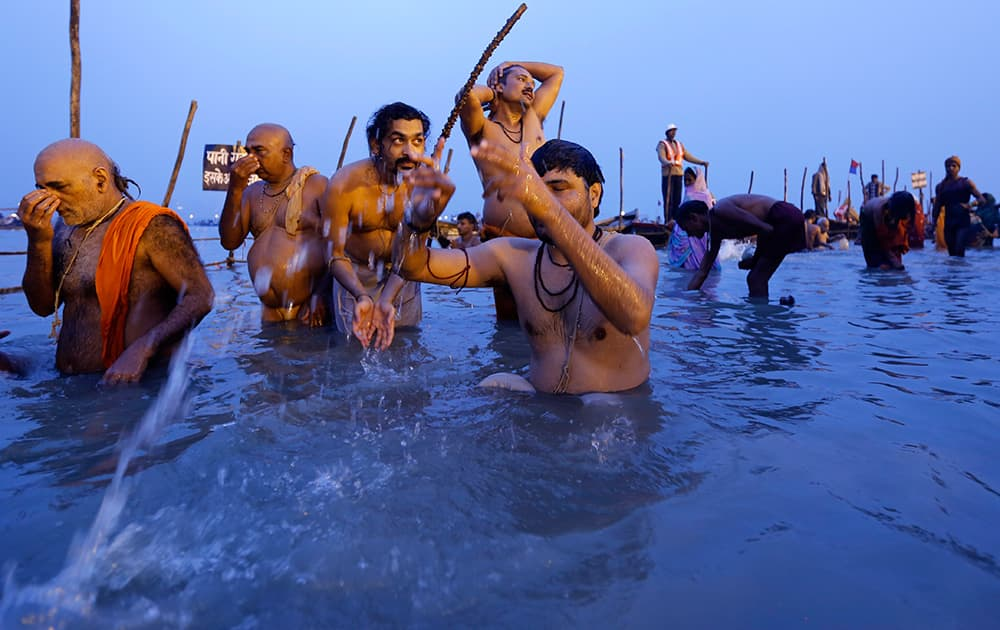 Hindu devotees offers prayers to the Sun god after taking a holy dip at the Sangam, the confluence of the Ganges and Yamuna rivers, on `Mauni Amavasya` or new moon day, the third and most auspicious date of bathing during the annual month long Hindu religious fair `Magh Mela` in Allahabad.