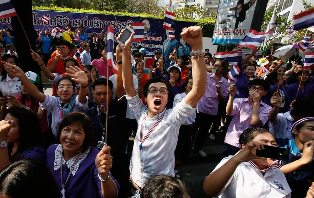 A supporter cheers on a passing anti-government march in Bangkok.