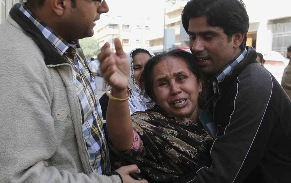 People comfort a woman who said she lost her husband in an attack in Karachi, Pakistan. Police said several members of the country`s security forces have been killed in separate attacks in the southern city of Karachi.