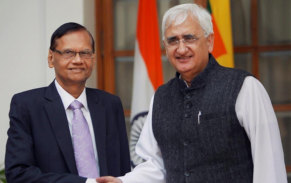 External Affairs Minister Salman Khurshid shakes hands with his Sri Lankan counterpart Gamini Lakshman Peiris in New Delhi.