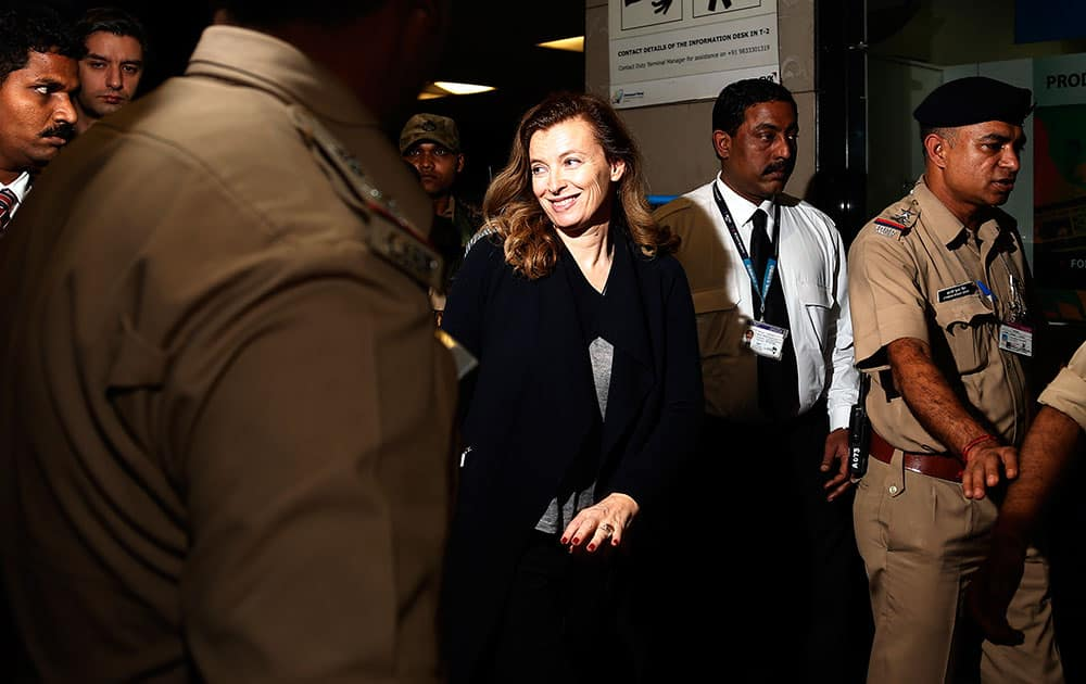France`s former first lady Valerie Trierweiler, centre, smiles as she arrives at the airport to board a flight in Mumbai, India.